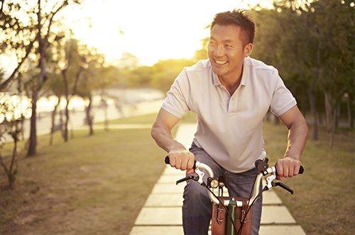 Happy man biking by the river.